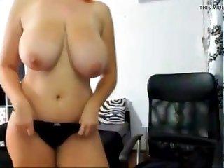 Busty redhead tittyfucks a dildo between her amazing tits