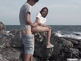 Young couple is making cherish on the rocky shore